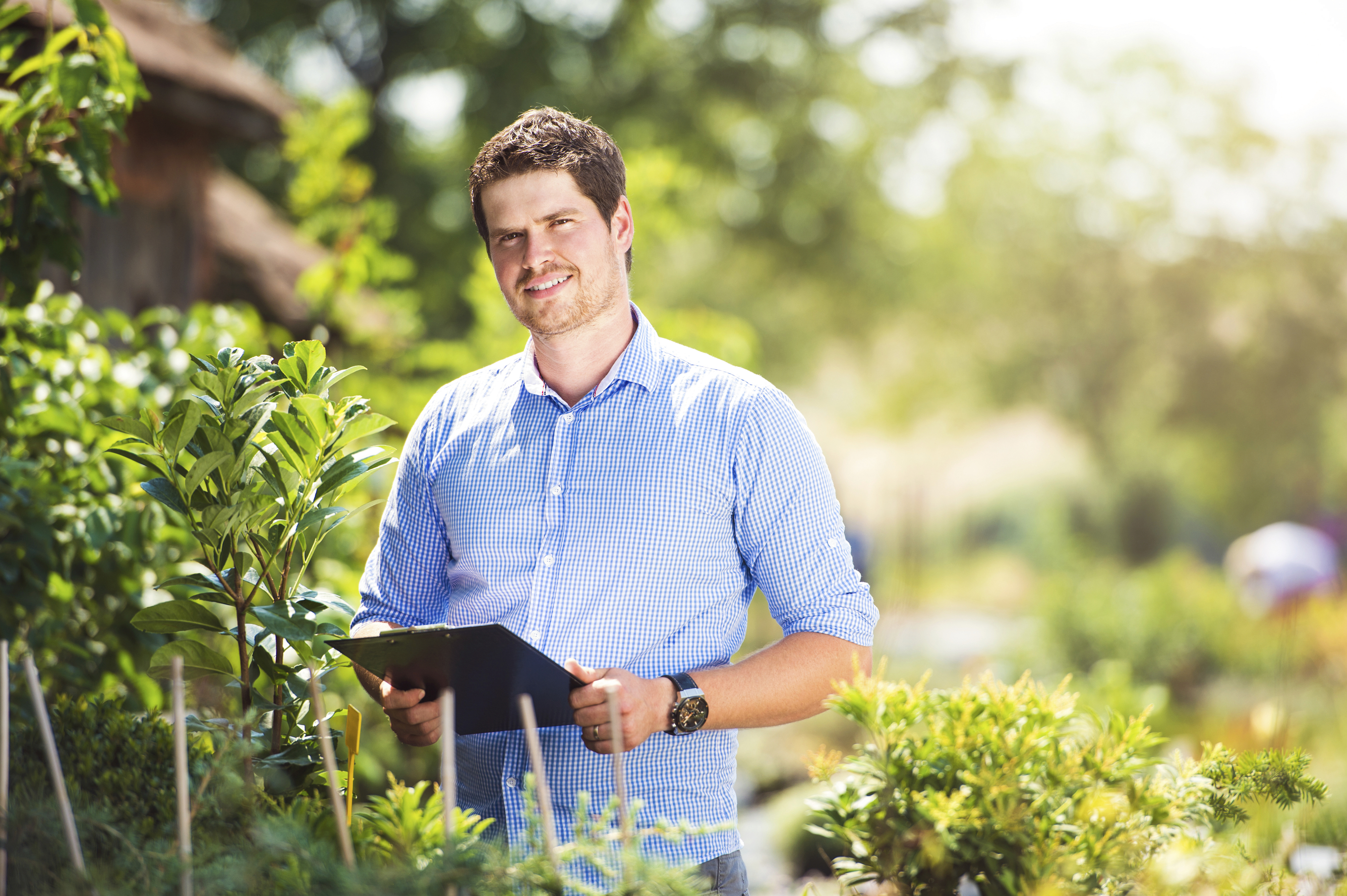Gardener-holding-clipboard,-in-his-garden,-green-sunny-nature-000088137377_Large.jpg